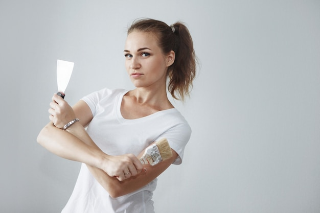 Junge schöne frau im weißen t-shirt, das mit pinsel und spatel in der neuen wohnung während der reparatur aufwirft