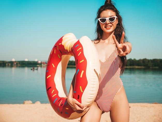 Junge schöne frau in badebekleidung und sonnenbrille, die am strand mit aufblasbarem donut aufwirft
