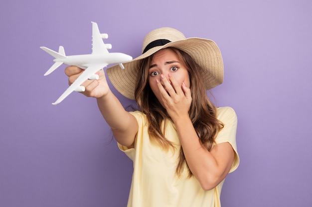 Junge schöne frau in beigem t-shirt und sommerhut, die ein spielzeugflugzeug hält und die kamera anschaut, die schockiert ist und den mund mit der hand auf violettem hintergrund bedeckt