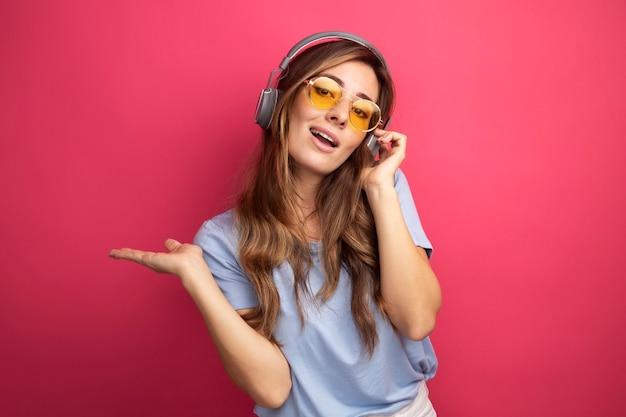 Junge schöne frau in blauem t-shirt mit gelber brille mit kopfhörern, die auf die kamera schaut und fröhlich auf rosafarbenem hintergrund lächelt