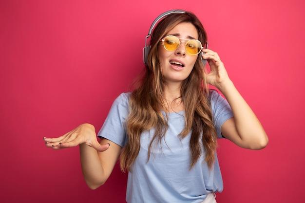 Junge schöne frau in blauem t-shirt mit gelber brille mit kopfhörern, die auf die kamera schaut und mit den händen selbstzufrieden auf rosafarbenem hintergrund gestikuliert