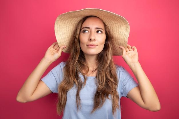 Junge schöne frau in blauem t-shirt und sommerhut, die mit einem lächeln auf dem gesicht auf rosafarbenem hintergrund beiseite schaut