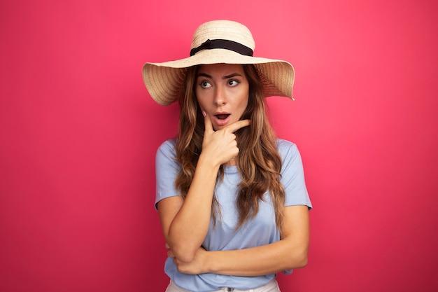 Junge schöne frau in blauem t-shirt und sommerhut, die überrascht beiseite schaut, stehend über rosa hintergrund