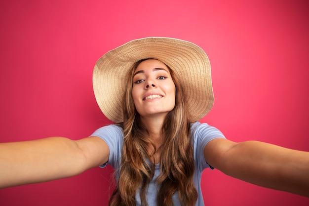 Junge schöne frau in blauem t-shirt und sommerhut mit blick in die kamera, die fröhlich lächelt und eine einladende geste macht