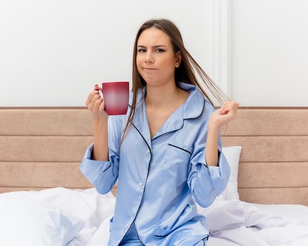 Junge schöne frau in den blauen pyjamas, die auf bett mit tasse kaffee suchen, der an der kamera unzufrieden ist, die im schlafzimmerinnenraum auf hellem hintergrund aufwacht