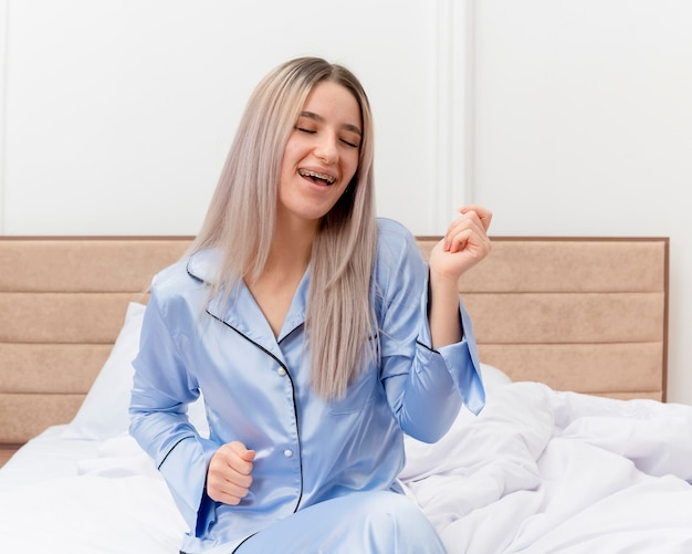 Junge schöne frau in den blauen pyjamas, die auf dem bett glücklich und aufgeregt lächelnd im schlafzimmerinnenraum auf hellem hintergrund sitzen