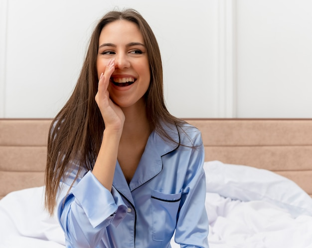 Junge schöne frau in den blauen pyjamas, die auf dem bett sitzen und mit der hand nahe mund glücklich und positiv im schlafzimmerinnenraum auf hellem hintergrund rufen oder schreien