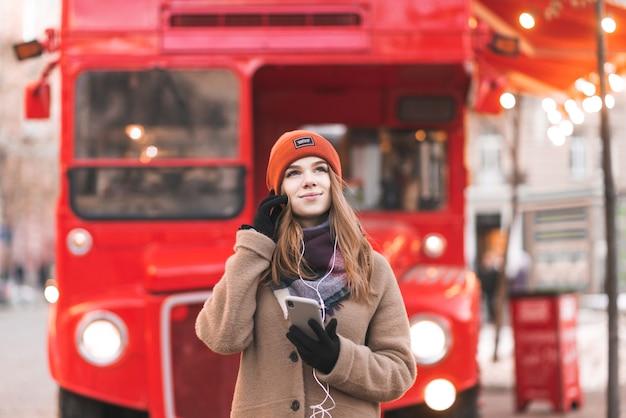Junge schöne frau in den warmen kleidern auf einem roten straßenhintergrund