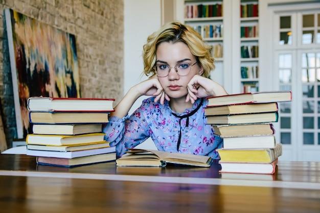Junge schöne frau in der bibliothek mit büchern