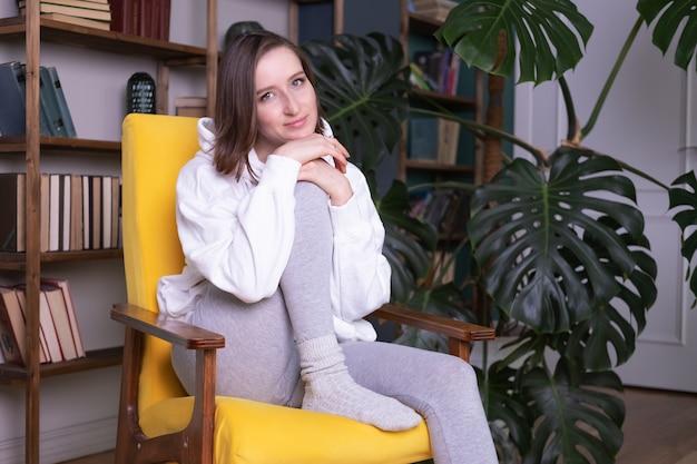 Junge schöne frau in der freizeitkleidung, die auf gelber couch im modernen innenraum sitzt.