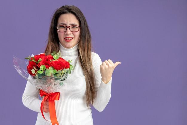 Junge schöne frau in der freizeitkleidung, die den strauß der roten rosen hält, die kamera verwirrt betrachten, die mit dem daumen auf das valentinstagkonzept der seite steht, das über lila hintergrund steht