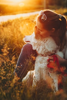 Junge schöne frau in der freizeitkleidung und in der sonnenbrille, die auf parkgras sitzt und weißen hund umarmt, der sonnenuntergang auf hintergrundbeleuchtet wegschaut