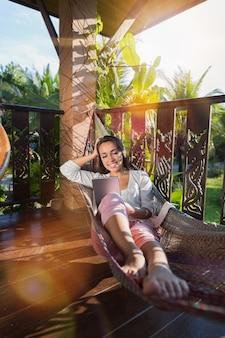 Junge schöne frau in der hängematte auf sommer-terrasse