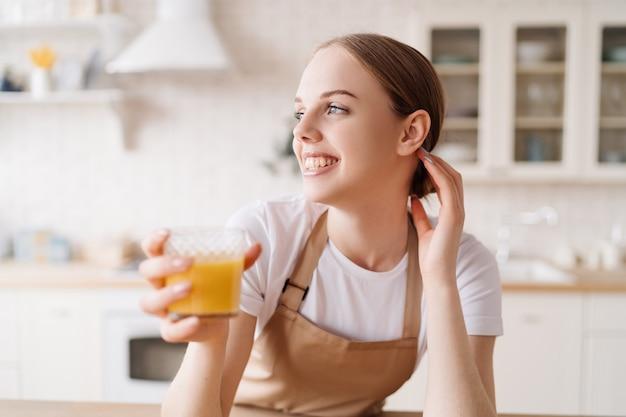 Junge schöne frau in der küche in einer schürze, obst und orangensaft