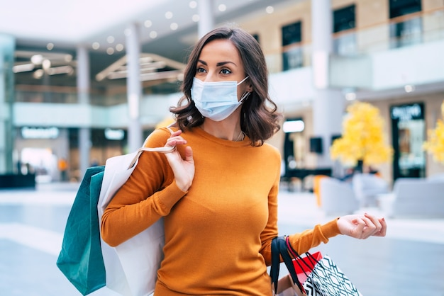 Junge schöne frau in der medizinischen sicherheitsmaske mit einkaufstaschen geht auf dem einkaufszentrum am schwarzen freitag