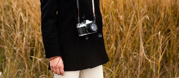 Junge schöne frau in der natur mit kamera-nahaufnahme