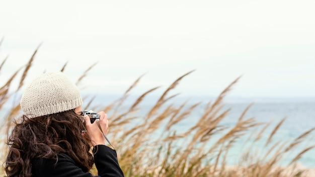 Junge schöne frau in der natur mit kamera