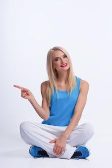 Junge schöne frau in der sportbekleidung, die auf dem boden sitzt, zeigt zur seite mit ihrem finger lokalisiert auf weiß