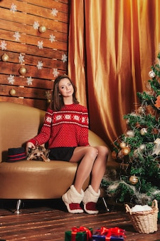 Junge schöne frau in der weihnachtsstrickjacke mit hübschem yorkshire-hund auf sofa