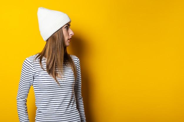 Junge schöne frau in einem gestreiften pullover und hut schaut weg auf einem gelben hintergrund