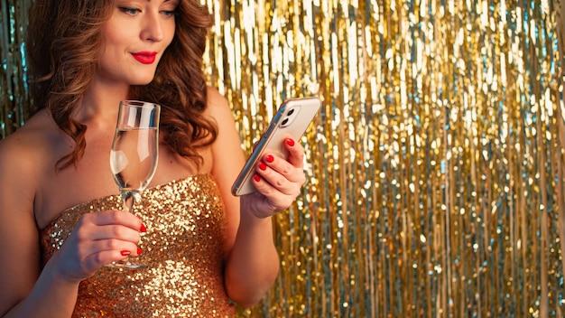 Junge schöne frau in einem goldenen kleid trinkt champagner, hält ein smartphone und hat spaß an einer party auf einem glänzenden goldenen hintergrund