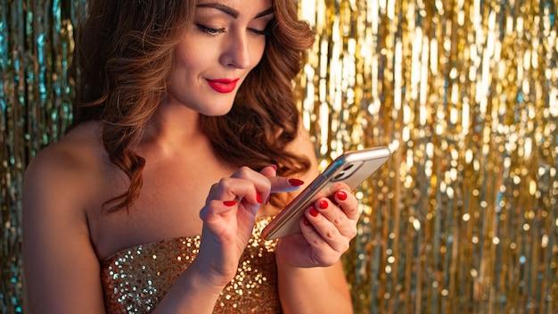 Junge schöne frau in einem goldenen kleid unter verwendung des telefons, das spaß an einer party auf einem glänzenden goldenen hintergrund hat