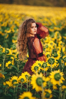 Junge schöne frau in einem kleid unter blühenden sonnenblumen. agro-kultur.