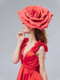 Junge schöne frau in einem roten kleid mit einer großen rosenblume