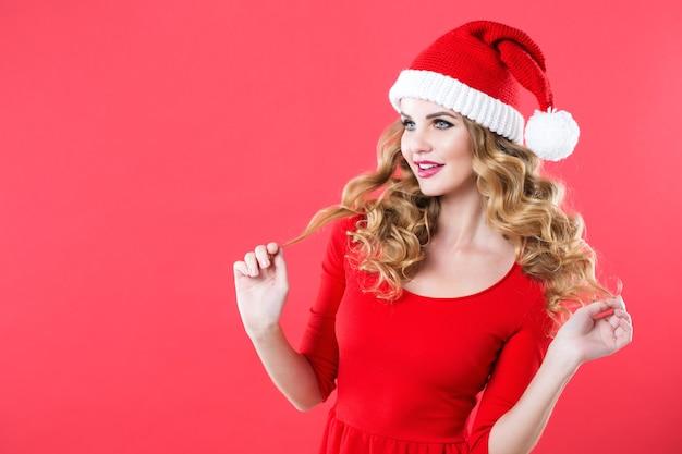 Junge schöne frau in einem roten kleid und in der weihnachtsmannmütze. konzept des neuen jahres und der weihnachtsferien.