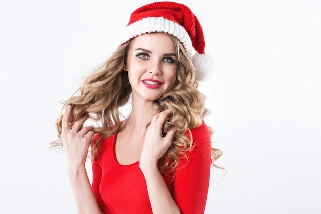 Junge schöne frau in einem roten kleid und in der weihnachtsmannmütze