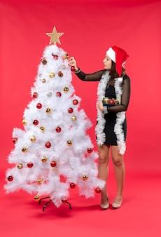 Junge schöne frau in einem schwarzen kleid mit weihnachtsmannhut und dekorierendem weihnachtsbaum