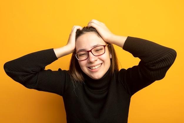 Junge schöne frau in einem schwarzen rollkragenpullover, der vorne glücklich und aufgeregt mit hand auf ihrem kopf steht, der über orange wand steht
