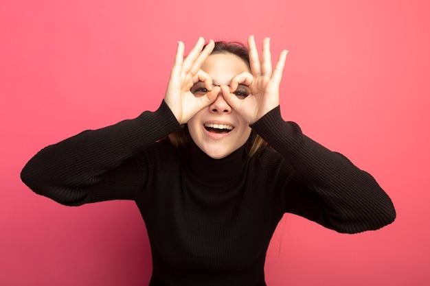 Junge schöne frau in einem schwarzen rollkragenpullover und in den gläsern, die vorne durch finger schauen, machen fernglasgeste, die über rosa wand steht
