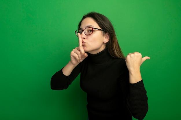 Junge schöne frau in einem schwarzen rollkragenpullover und in der brille, die zurück zeigen, machen stille geste mit finger auf lippen, die über grüner wand stehen