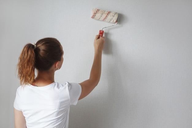 Junge schöne frau in einem weißen t-shirt malt eine wand mit einer walze in einer neuen wohnung während einer renovierung