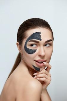 Junge schöne frau in einer maske für das gesicht des therapeutischen schwarzen tons. beauty gesicht hautpflege. spa-behandlung . mädchenmodell mit feuchtigkeitscreme kosmetischer maske.