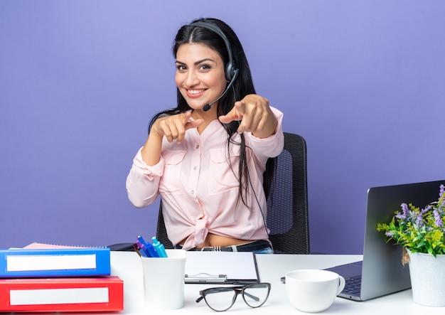 Junge schöne frau in freizeitkleidung, die ein headset mit mikrofon trägt, das mit zeigefingern zeigt, die selbstbewusst am tisch sitzen und mit laptop auf blau lächeln