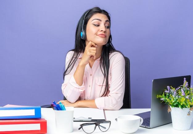 Junge schöne frau in freizeitkleidung, die ein headset mit mikrofon trägt und mit verwirrtem ausdruck beiseite schaut, sitzt am tisch mit laptop über blauer wand und arbeitet im büro
