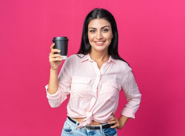 Junge schöne frau in freizeitkleidung, die eine kaffeetasse hält und fröhlich lächelt, die auf rosa steht