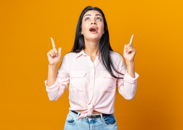 Junge schöne frau in freizeitkleidung, die glücklich und überrascht aufschaut und mit den zeigefingern auf etwas zeigt, das über der orangefarbenen wand steht?
