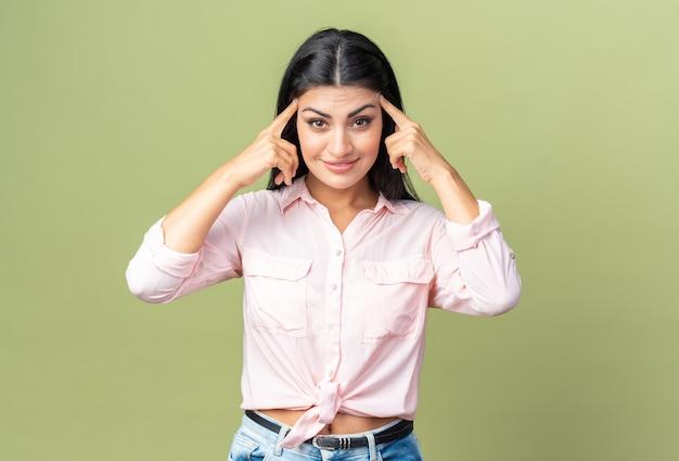 Junge schöne frau in freizeitkleidung, die lächelnd selbstbewusst aussieht und mit dem zeigefinger auf ihre schläfen zeigt