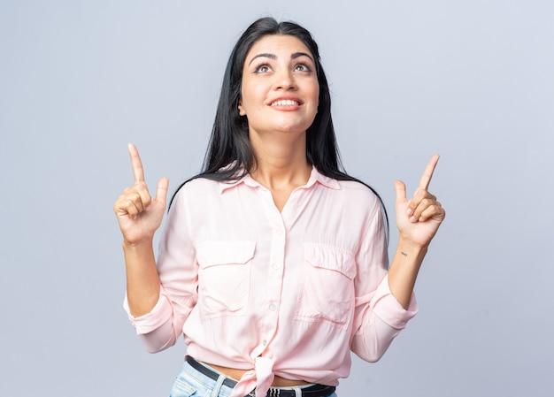 Junge schöne frau in freizeitkleidung, die nach oben schaut und fröhlich mit den zeigefingern nach oben zeigt, glücklich und positiv