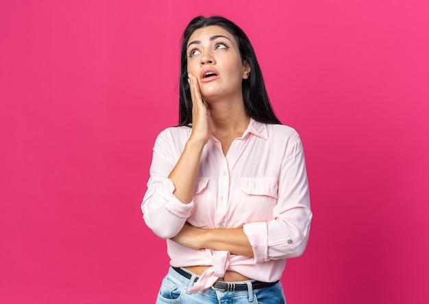 Junge schöne frau in freizeitkleidung, die verwirrt über rosa wand steht