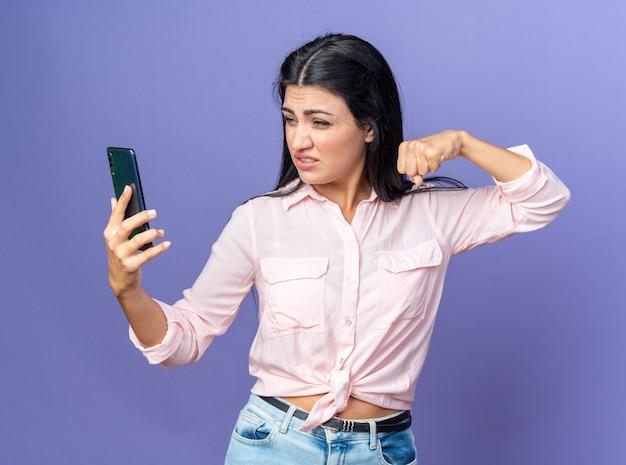 Junge schöne frau in freizeitkleidung macht selfie mit smartphone und zeigt geballte faust