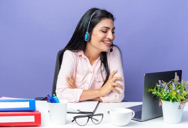 Junge schöne frau in freizeitkleidung mit headset mit mikrofon am tisch sitzend mit laptop, der auf den bildschirm schaut und fröhlich lächelt und einen videoanruf auf blau hat