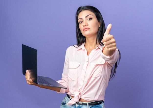 Junge schöne frau in freizeitkleidung mit laptop sieht selbstbewusst aus und zeigt daumen hoch