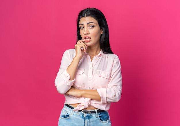 Junge schöne frau in freizeitkleidung verwirrt stehend auf rosa