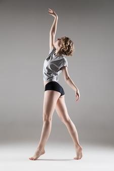 Junge schöne frau in grauem t-shirt und schwarzen shorts tanzen, studioserie