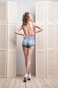 Junge schöne frau in jeans-shorts und top posiert vor einer jalousie. rückansicht