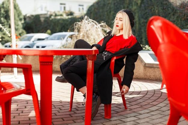 Junge schöne frau in modischer herbstkleidung in einem schwarzen mantel sitzt auf einem roten stuhl in einem café